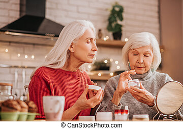 Two good-looking elderly women applying new cream