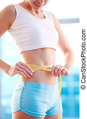 Good results  - Image of slender woman measuring her waist