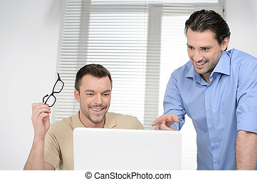 Good results! Two cheerful business people discussing something on the computer and smiling