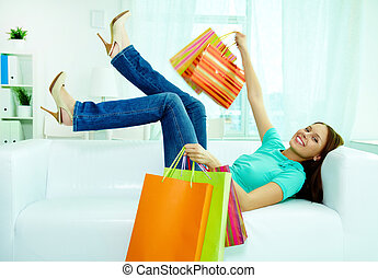 Good sale - Portrait of happy shopper with paperbags lying ...