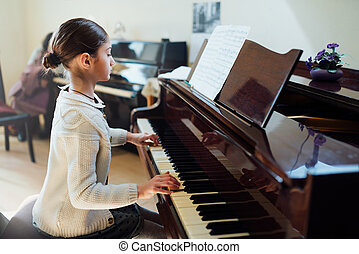 good student plays piano at a music school - good student...