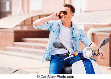 Good talk with friend. Cheerful young man sitting on scooter and talking on the mobile phone