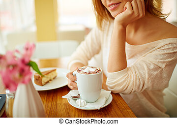 Good time - Image of young female with cup of latte sitting...