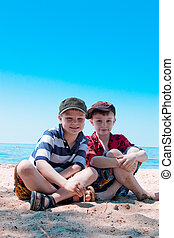 Good times on the beach - Two brothers sitting on the beach