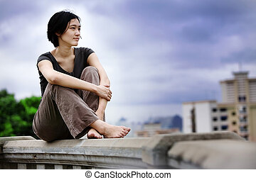 Asian girls sits at lookout overlooking city
