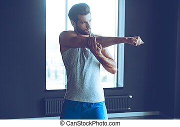 Good warm-up. Young handsome man in sportswear stretching his arm at gym