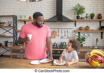 Tall dark-skinned man in a pink tshirt standing and his kid wiping the plate
