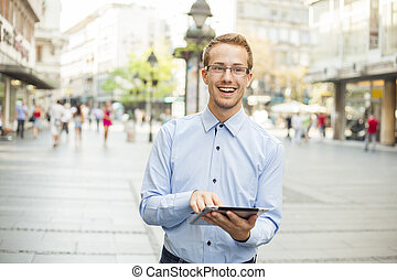 Goodlooking men with tablet computer on urban street