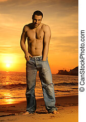 Goodlooking shirtless man at sunset