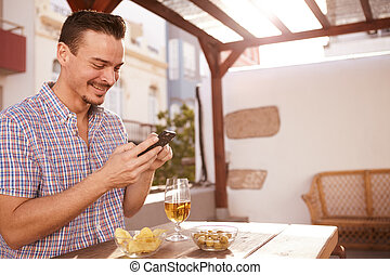 Goodlooking smiling young man with cellphone