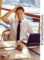 Goodlooking young man relaxing at restaurant, sitting with laptop computer