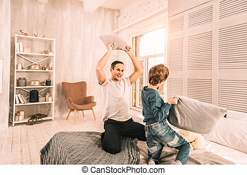 Goofy boy and his dad having a very intense pillow fight.