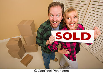 Goofy Couple Holding Sold Sign Surrounded by Boxes