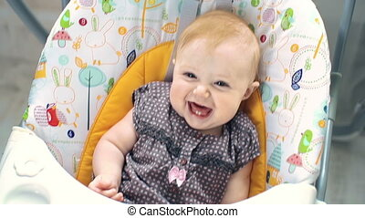 Goofy Face - High angle view of happy baby giggling in the...
