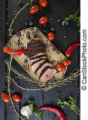 Goose breast Christmas roast with blueberries, tomatoes, red peppers and rosemary served on a wooden board