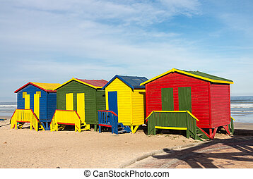 Row of four colorful beach huts by sea at Gordons Bay near Cape Town South Africa