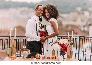 Goregous black wedding couple happily smiling and holding...