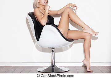 Gorgeous and bossy. Side view cropped image of gorgeous young blond hair woman in lingerie sitting in chair