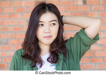 Gorgeous asian woman portrait over a brick wall