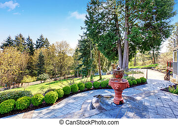 Gorgeous back yard with patio including elegant fountain and greenery.