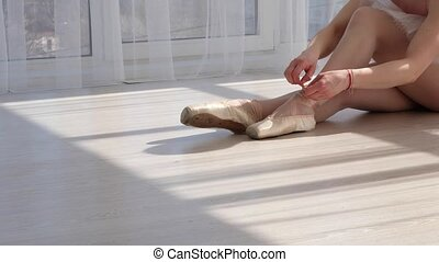 Gorgeous ballet dancer in tutu sitting on the floor and...