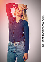 Gorgeous beauty. Studio shot of beautiful young woman wearing black shirt holding hand over head and looking at camera