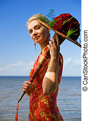 Gorgeous blond girl with a bouquet of roses on the beach