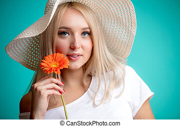 gorgeous blond model wearing hat and white T-shirt looking at the camera