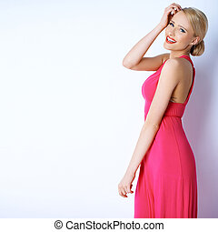 Gorgeous blond sexy woman posing in pink dress