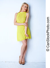 Gorgeous blond woman posing in yellow dress