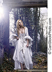 Gorgeous blonde beauty in a old-fashioned dress in a forest