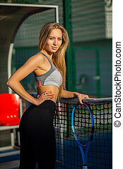 Gorgeous blonde fitness model with perfect long hair posing with a tennis racket at the court