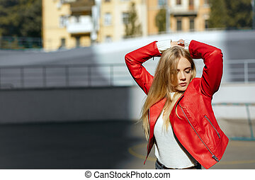 Gorgeous blonde girl with long hair wearing red leather jacket, posing in rays of sun. Empty space