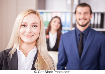 Gorgeous blonde manager in front of her team in the office