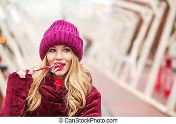 Gorgeous blonde woman in red knitted hat posing with candy cane at the street