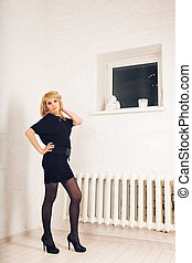 Gorgeous blonde woman in the room. Beauty, fashion.
