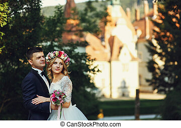 Gorgeous blonde young bride and charming groom posing at sunset fairy tale castle background