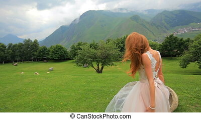 Gorgeous bride blonde posing while looking at mountains. Attractive girl on a background of mountain scenery. Wedding day