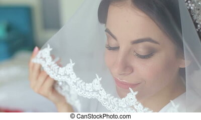 Gorgeous bride portrait with make-up in the morning in room near window.