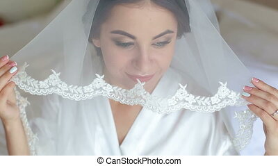Beautiful woman getting ready for wedding day, holding veil and smiling.