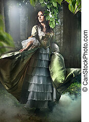 Gorgeous brunette beauty in a old-fashioned dress in a forest