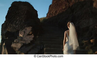 Gorgeous brunette bride goes up the hill on mountain volcano landcape in Santorini, Greece close up