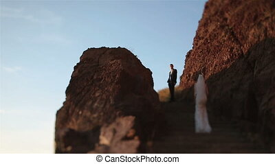 Gorgeous brunette bride goes up the hill to her groom on mountain volcano landcape in Santorini, Greece close up