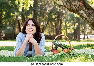 Gorgeous brunette lying on a mat with basket full of fruits in the park