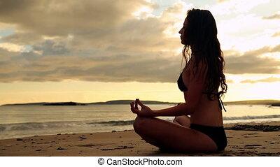 Gorgeous brunette meditating on the beach