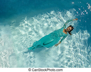 Gorgeous Brunette Model Swimming In A Pool Wearing A Formal Gown