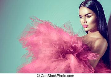 Gorgeous brunette model woman in pink dress posing in studio