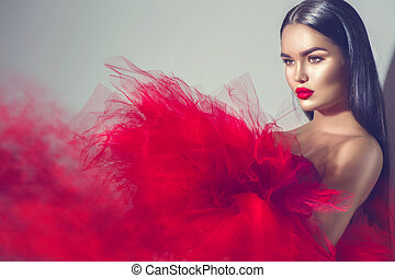 Gorgeous brunette model woman in red dress posing in studio
