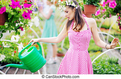 Gorgeous brunette watering the flowers
