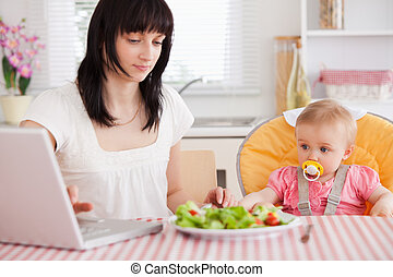 Gorgeous brunette woman eating a salad next to her baby while relaxing with her laptop in the kitchen